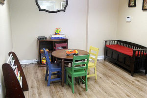 Children's play area with table and four chairs, bench, toy shelf, and magazine rack