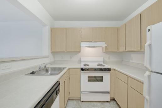 bright kitchen, white appliances, light brown cabinets
